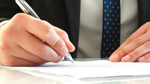businessman signing paper